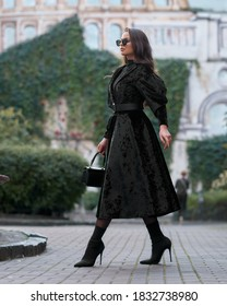 Stylish woman in black short coat with belt, skirt, tights, sunglasses and high heels walking at city street.