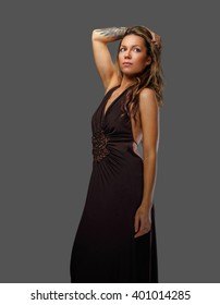 Stylish woman in a brown dress with tattoo on her hand. Isolated on a grey background.
