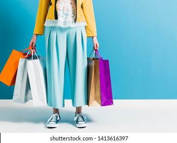 Stylish woman carrying a lot of colorful shopping bags, sales and fashion concept