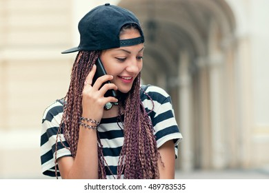 Stylish woman with cornrows talking by smartphone on the street