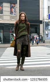 Stylish woman crosses the road at a crosswalk. She is dressed in the style of boho: brown coat, yellow bag, green sweater, shorts and torn stockings