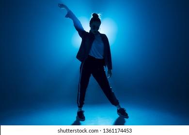 Stylish woman dancing solo on hip hop party. Sunglasses, modern black dance wear, neon lights.