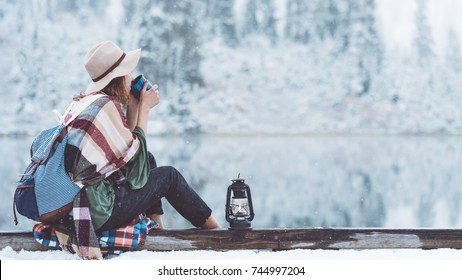 Stylish woman drinking hot coffee and sitting next to stunning winter landscape. Traveling in mountains wilderness. Wanderlust and boho style