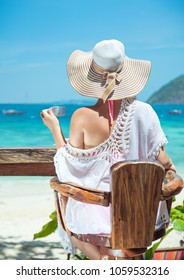 Stylish woman enjoying coffee on tropical beach