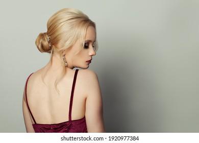 Stylish woman fashion model with blonde hairdo on white background portrait