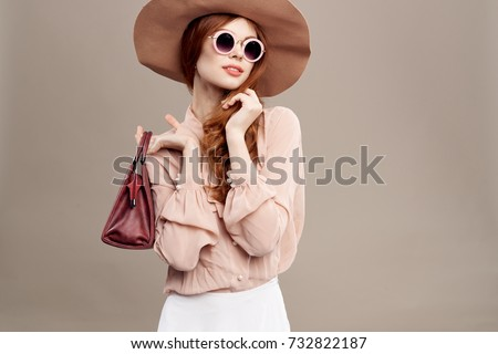 5254930b3a8f stylish woman with glasses hat holds a purse on a light background
