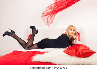 Stylish woman in gorgeous fashion black dress with bright makeup hairstyle in hotel apartment. Sexy slim girl relaxing on bed at home luxury interior. Fashion model.