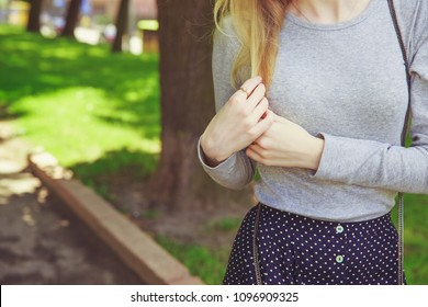 Stylish woman in gray shirt and dark polka dot skirt walking in the park. Street look, casual fashion concept. Woman's hands and long blonde hair