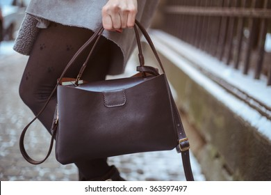 Stylish woman in gray trendy warm coat with dark brown leather bag walking down the snowy street
