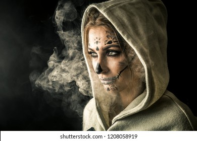 Stylish woman with halloween make up posing isolated on black background with the smoke around her and beautiful studio light.