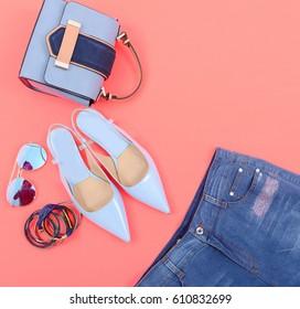 Stylish woman Handbag and cosmetics,makeup accessories,jeans on orange background