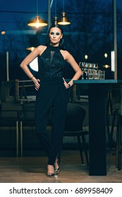 Stylish woman having shining black hair posing like a model inside opulent room. Lady dressed in black jumpsuit standing on one leg in high heels. Lovely night view through the glass window.