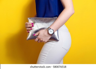 Stylish woman hold silver clutch bag. Summer spring outfit