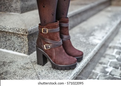 Stylish woman with legs in brown nylon stockings and brown ankle boots with high heels. Winter fashion outfit