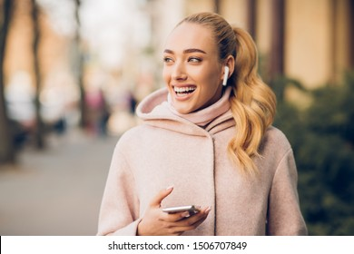 Stylish woman listening music on her airpods, walking in city at autumn day