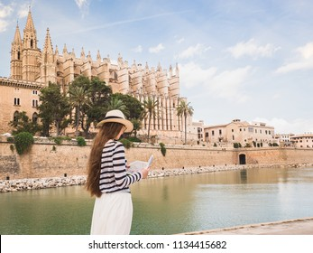 Stylish woman looking at the map with sights on the background of palm trees and historical buildings. Spain, Palma de Mallorca