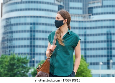 A stylish woman in a medical face mask walks thrusting a hand into a pocket of trousers, holds a bag in downtown. Girl keeping social distance wears a face mask to avoid the spread of coronavirus