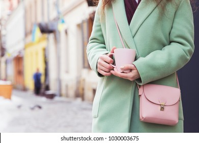 Stylish woman in mint winter oversize coat with pink leather purse or handbag posing on the street. Trendy winter outfit. Woman drinking coffee on the street, coffee to go