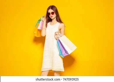 stylish woman with multicolored packages on a yellow background, shopping