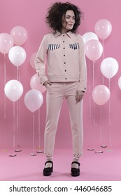 stylish woman on pink background with balloons