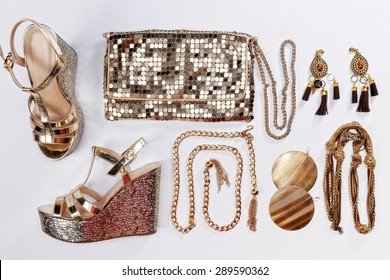 Stylish woman outfit. Golden jewelry, shiny gold purse and sandals, isolated on white background.