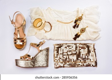 Stylish woman outfit. White summer dress, sandals, golden jewelry and shiny gold purse, isolated on white background.