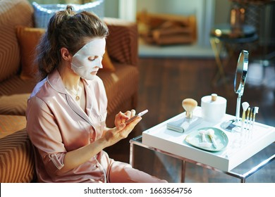 stylish woman in pajamas with white sheet facial mask on face cloud download to smartphone from stored data on server in the modern living room in sunny winter day.