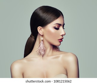 Stylish Woman with Ponytail Hairstyle and Pink Earrings