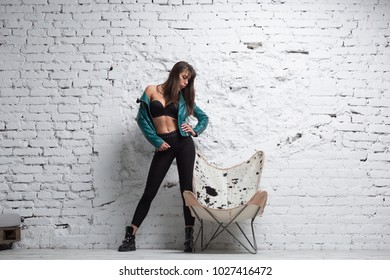 Stylish woman posing over white grungy brick wall