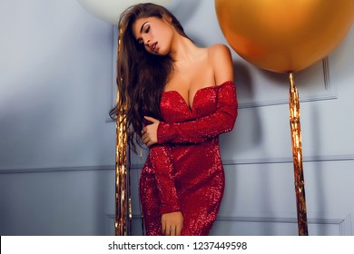 Stylish woman in red party dress with deep decollete, open shoulders and sleeves. Head tilted on side, long curly hair laying on the body. Hand on the arm. Makeup on the face, big lips. Two balloons