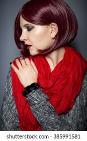 Stylish woman in red wearing an electronic smartwatch wearable tech.  The wrist watch is an electronic device with a touch screen digital display.