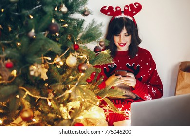 stylish woman in reindeer hat holding phone and laptop, under christmas tree lights. shopping online, sale. space for text. seasonal greetings, happy holidays. social media