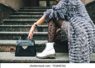 stylish woman in rich fur coat in city street, autumn fashion trend, black leather purse, white boots, urban style, accessories, legs, footwear, details close up