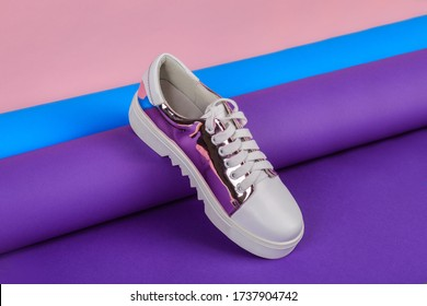Stylish woman shoe on a colorful paper roll. Creative footwear design concept.