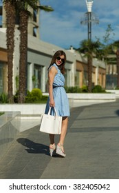 Stylish woman with shopping bags in summer city