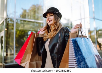 Stylish woman with shopping bags walks through the city streets. Spring Style.  Consumerism, purchases, shopping, lifestyle concept.