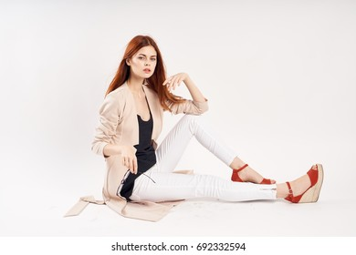 Stylish woman sits on the floor on a light background, studio, fashion, style
