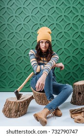 Stylish woman sitting in autumn outfit on wooden stumps and looking at camera