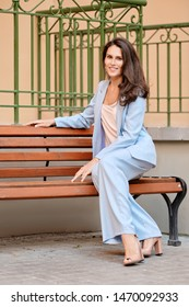 Stylish woman in skyblue pantsuit having rest on a bench near the office