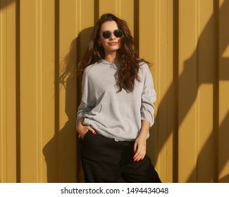 Stylish woman standing against yellow metal wall at sunset with beautiful shadows. Girl in gray hooding, black trousers, sneakers ans sunglasses relaxing, leaning on wall,