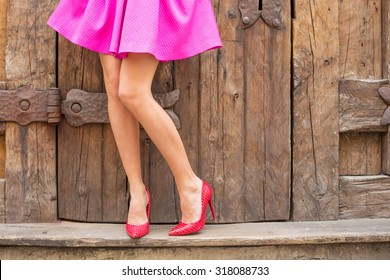 Stylish woman standing in front of old wooden doors