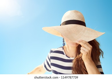 stylish woman in straw hat against blue sky hiding behind straw hat