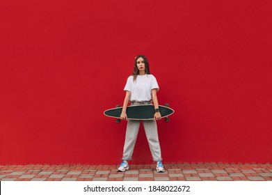 Stylish woman in street casual clothes posing at camera with a longboard in her hands on a red wall background. Portrait of a skater woman on a red background.