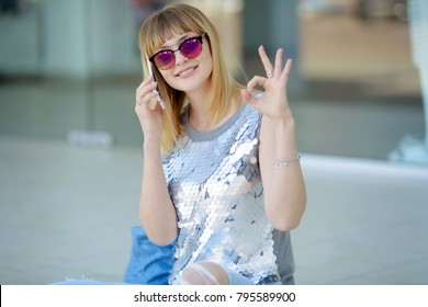 Stylish woman in sunglasses emotionally talking on the phone
