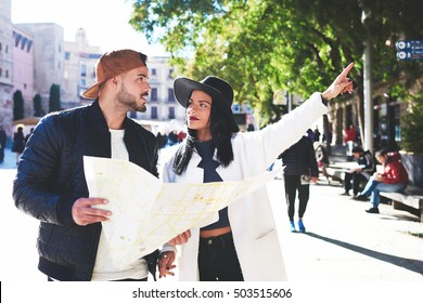 Stylish woman tourist ask her friend about historical buildings of city. Hipster man with a beard shows his sweetheart popular places of Barcelona. Lovers looking on map which attractions to visit