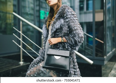 stylish woman walking in city in fur coat, urban street style, winter fashion trend, holding leather bag, accessories