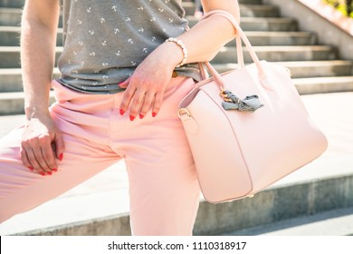 Stylish woman wearing in pink clothes with pink bag in her hands. Fasion cloth set and accessories.
