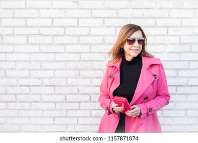 stylish woman wearing pink raincoat holding wallet