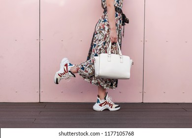 Stylish woman with a white bag in a vintage dress with fashionable sneakers posing near the pink wall. Close-up. The concept of shopping