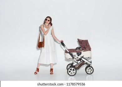 stylish woman in white dress and sunglasses posing with baby carriage on grey